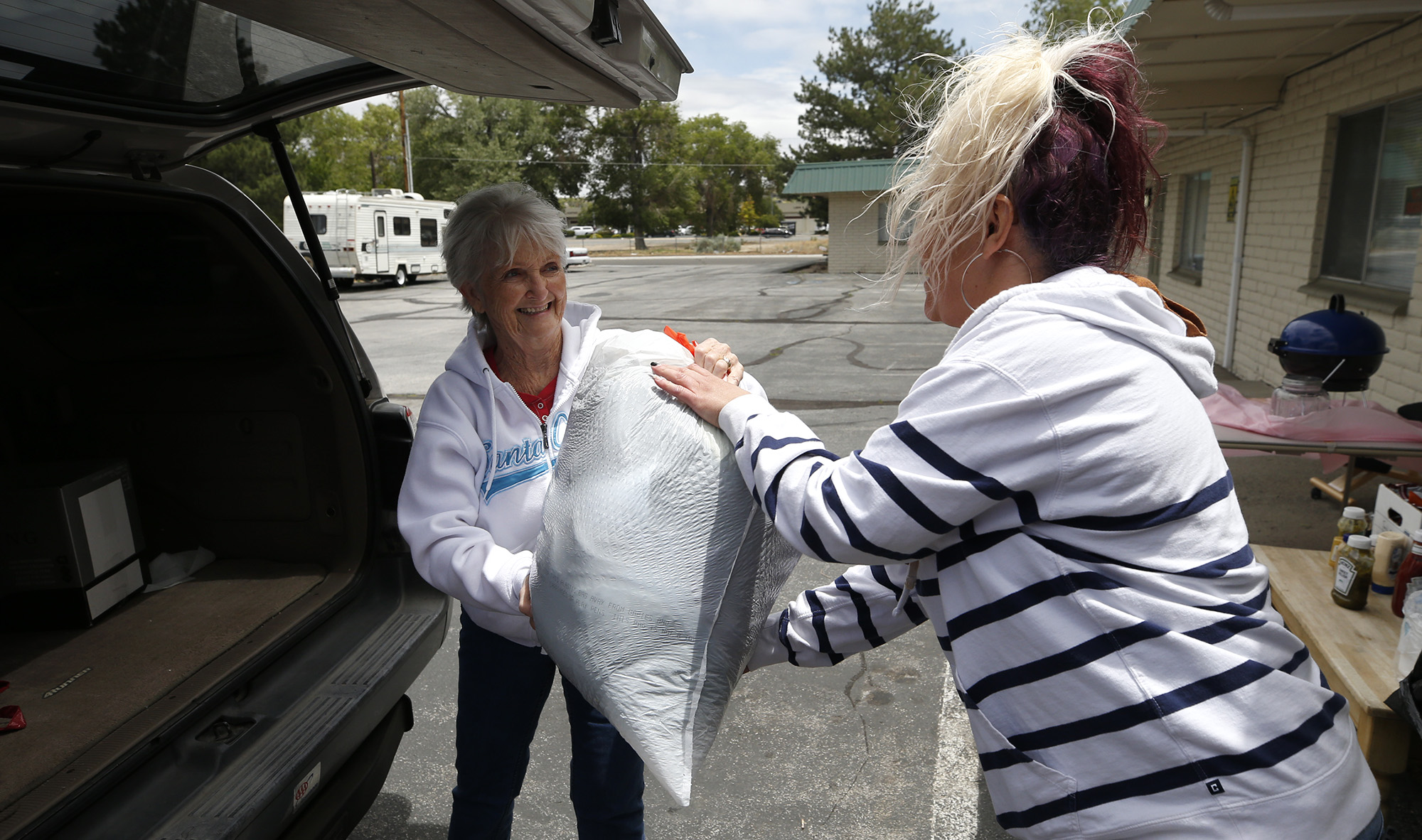 Pam France drops off donations to Jodi Miller at the rummage sale benefitting Lighthouse Lodge, in Carson City, Nev., on Saturday, June 13, 2020. Organizers hold a weekly BBQ and ongoing rummage sale to raise funds for creating a re-entry program for Carson City women being released from incarceration.  Photo by Cathleen Allison
